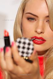 Beautiful blonde woman applying red lipstick in compact mirror  (CS_101784)