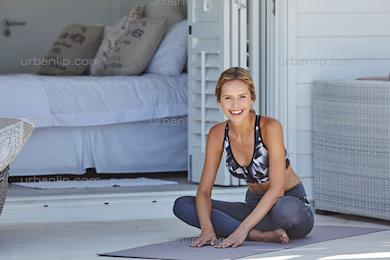 Beautiful woman sitting on yoga mat and smiling to camera (CU_100026)