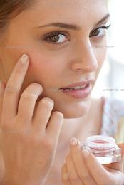 Close up of woman applying cream blush (AB_101257)