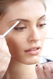 Close up of woman filling in her eyebrows (AB_101243)