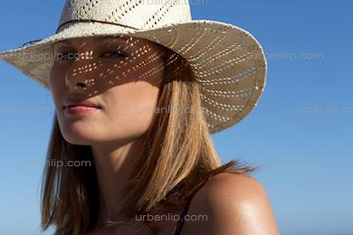 Woman wearing sunhat casting dappled light on face (AS_103118)