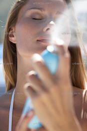 Portrait of woman spraying face with cooling mist  (AS_103948)