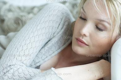Natural woman relaxing on white settee (AS_105074)