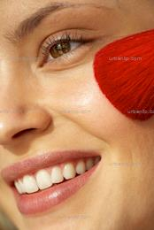 Close up of blonde girl using bright red face brush (AB_100262)