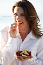 Mature woman eating a bowl of fruit (AV_100220)