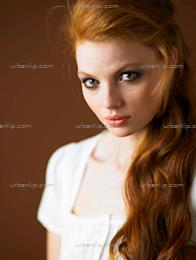 Close up of redhead woman with an updo & amber background (BA_100560)
